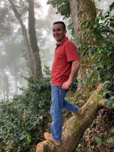 Finca Manager, Kelly Hartmannstanding on a log